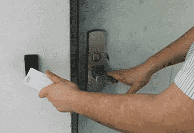 Image of a man waving a card key over a wall-mounted card reader.